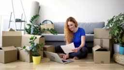 Cheerful young woman sitting on floor of new apartment with laptop and floor plan