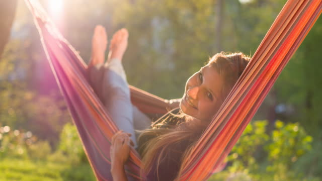 cheerful young woman swinging in a hammock among lush greenery and smiling into camera - hammock stock videos & royalty-free footage
