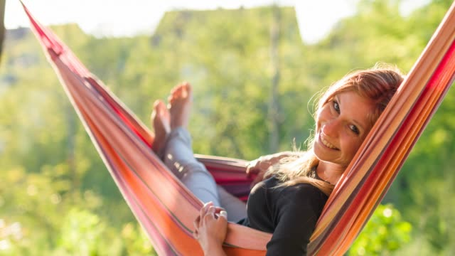 Cheerful young woman swinging in a hammock among lush greenery and smiling into camera