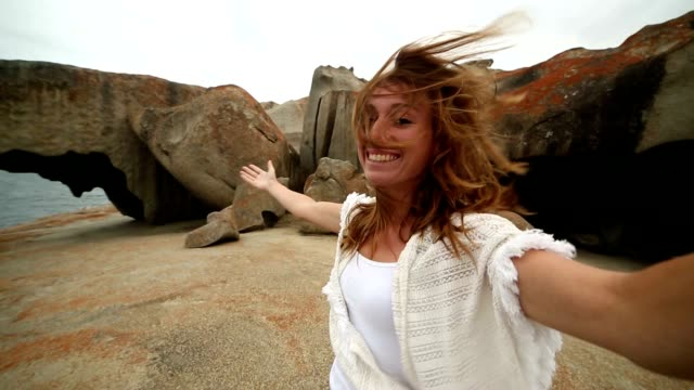 Cheerful young woman takes selfie portrait at The Remarkable rocks