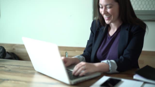 Glad ung kvinna att skriva e-brevet med laptop