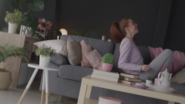 vidéos et rushes de jeune femme gaie se terminant sur un sofa après une longue journée - sauter