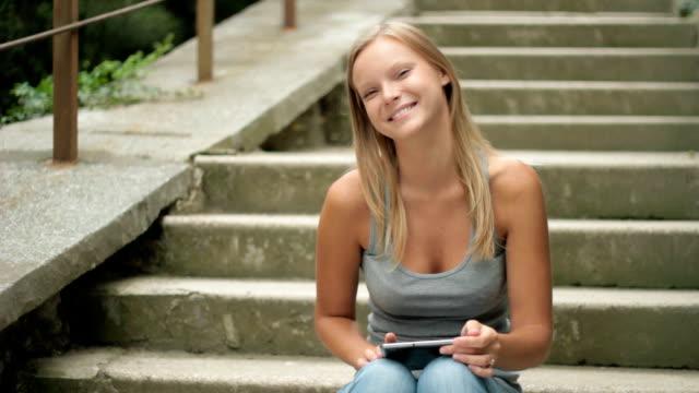allegro giovane donna con digital tablet sorridente - lettore di libri elettronici video stock e b–roll