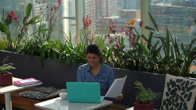 vídeos de stock, filmes e b-roll de mulher nova alegre que trabalha em um escritório de coworking com um portátil e os originais que sorriem - coworking space