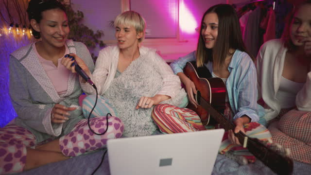 cheerful young women singing karaoke at a slumber party - slumber party stock videos & royalty-free footage