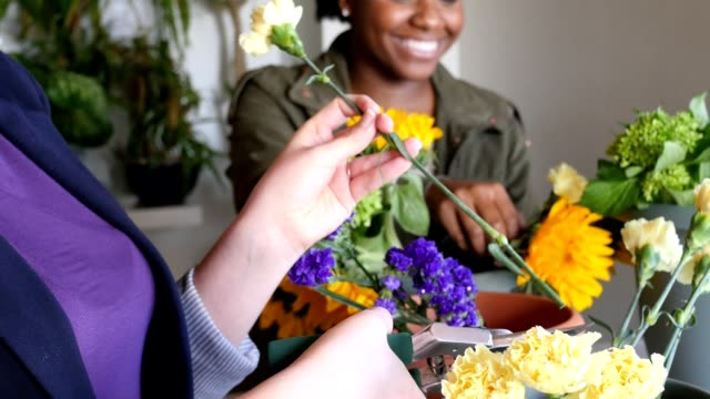 Cheerful young women working in flower shop, creating bouquets of cut flowers