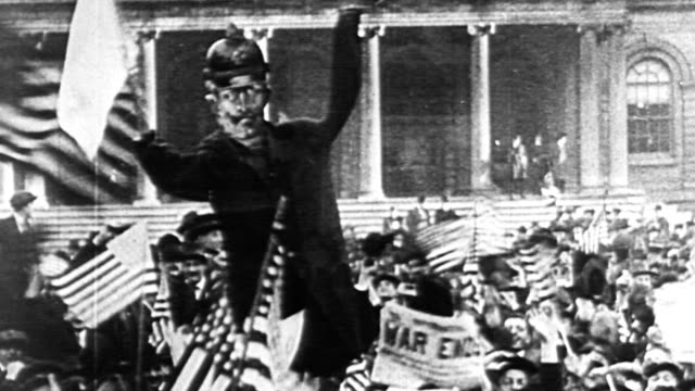 montage cheering crowds celebrating the end of world war i on armistice day / crowds waving american flags holding up newspaper headlines / streamers... - erster weltkrieg stock-videos und b-roll-filmmaterial