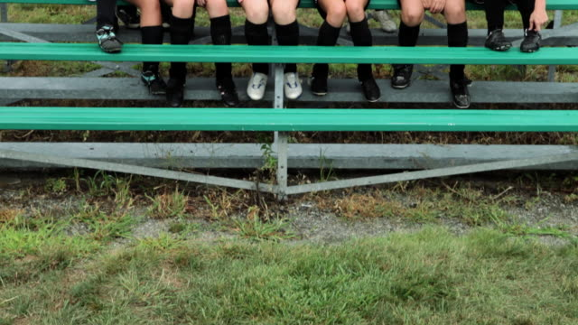 Cheering girl soccer players on bleachers