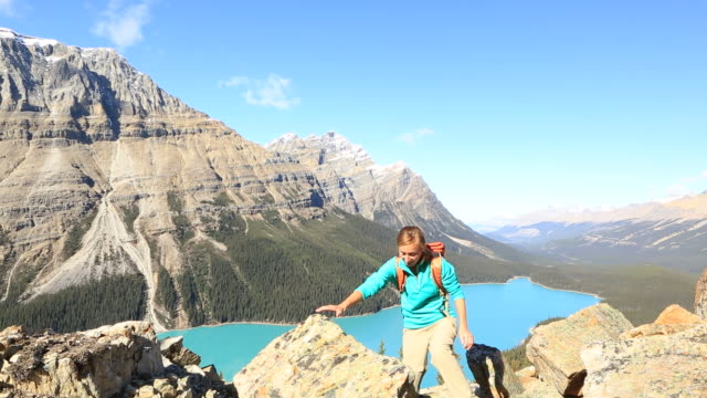 Cheering hiker on mountain top arms outstretched