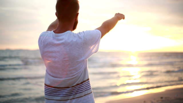 Cheering man open arms to sunset at seaside