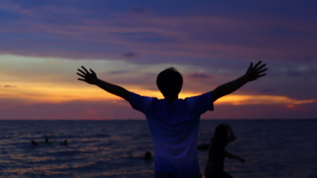 HD : Cheering man open arms to sunset at seaside with group of people background