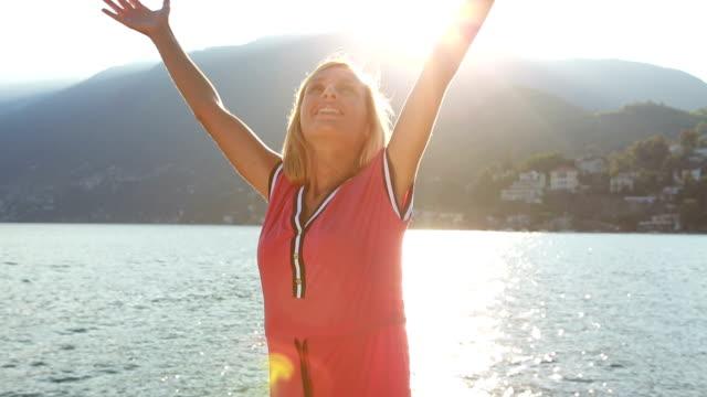vídeos de stock, filmes e b-roll de comemorando mulher os braços levantados pelo lago ao pôr do sol de verão - mãos estendidas
