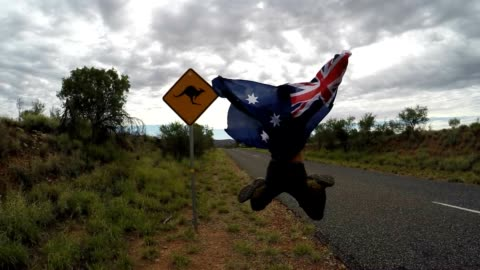 cheering young man jumping mid-air on the road, australia - road warning sign stock videos & royalty-free footage