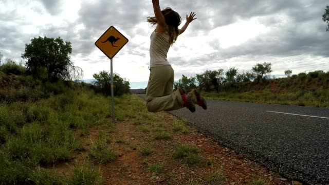 cheering young woman jumping mid-air on the road, australia - road warning sign stock videos & royalty-free footage