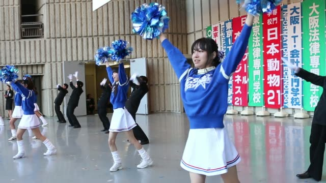 cheerleaders and dancers perform on stage during a rally to start off jobhunting in tokyo japan on wednesday jan 29 vocational students cheer smile... - チアリーダー点の映像素材/bロール