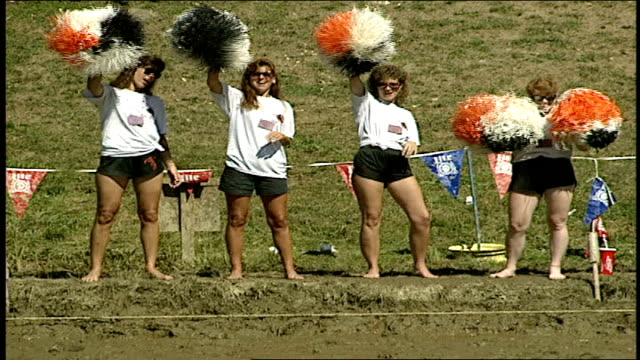 cheerleaders ceering as a row of men fall into the mud one by one - cheerleader stock videos & royalty-free footage