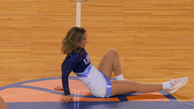 vidéos et rushes de cheerleaders dancing on the basketball court during half-time - compétition
