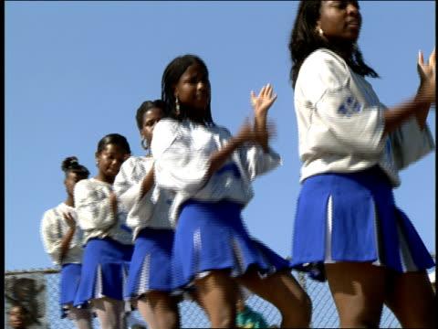 cheerleaders doing an attack cheer - チアリーダー点の映像素材/bロール
