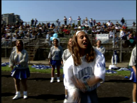 cheerleaders during high school football game - sportlerin stock-videos und b-roll-filmmaterial