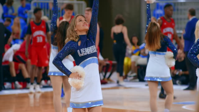 Cheerleaders performing their routine on the basketball court during a break