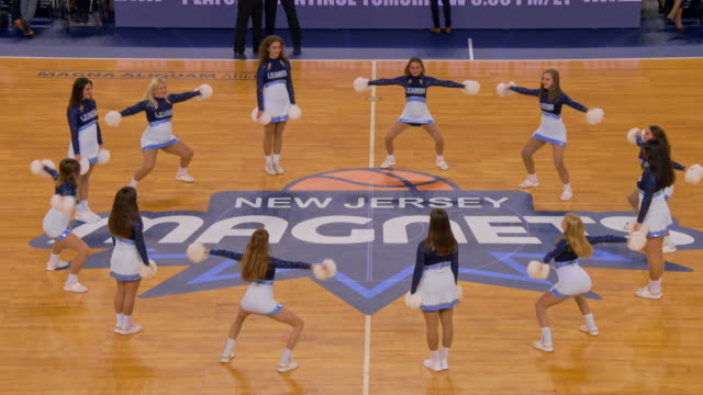 cheerleaders performing their routine with pom poms on the basketball court - pom pom stock videos & royalty-free footage