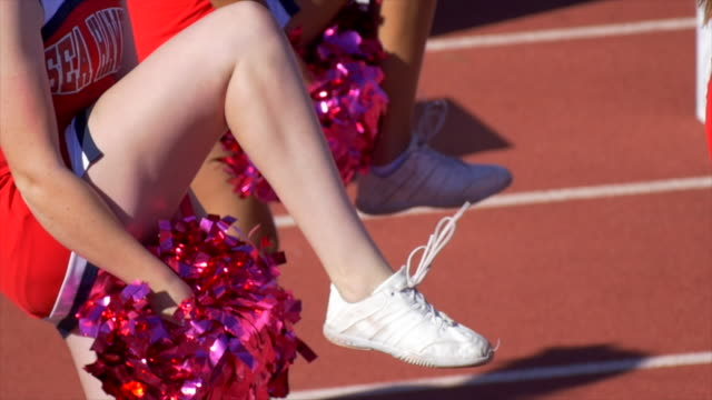 cheerleaders with pom-poms at an american football game. - slow motion - cheerleader stock videos and b-roll footage