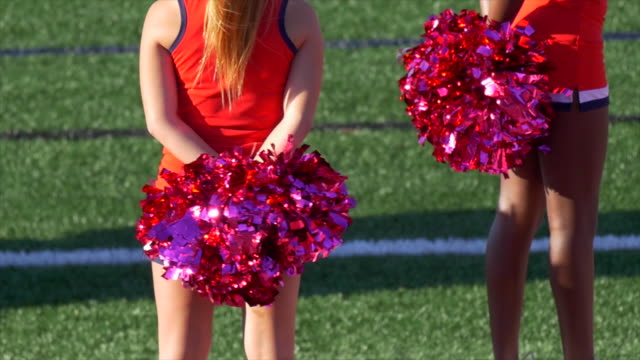 cheerleaders with pom-poms at an american football game. - slow motion - ragazza pon pon video stock e b–roll
