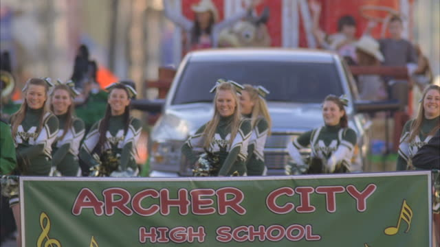 ms td pan cheerleaders with truck pulling float during parade / fillmore, california, usa - チアリーダー点の映像素材/bロール