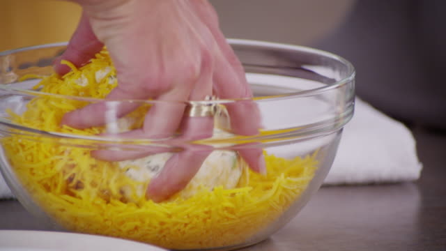 A cheese ball is turned into a bowl of grated cheddar cheese.