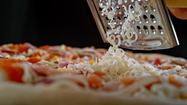 slo mo cheese rivs på en pizza - cheese bildbanksvideor och videomaterial från bakom kulisserna