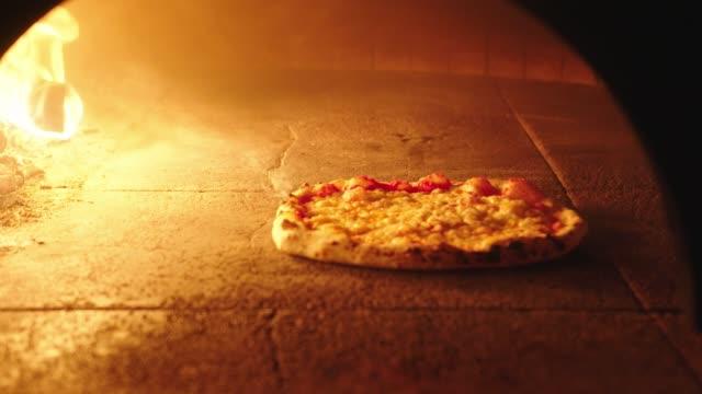 薪オーブンで焼くナポリのピザにチーズバブリング - 盛り付け点の映像素材/bロール