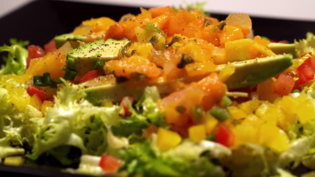 vídeos y material grabado en eventos de stock de cheese crumbles fall onto a rotating platter of fiesta salad made of lettuce, avocado, tomatoes, and mango salsa. - aguacate