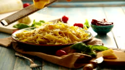 Cheese grating Just cooked Pappardelle italian cuisine dish on the rustic table