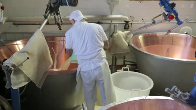 cheese makers stir vats of whole milk with spino tools curds rise to the top of copper cauldrons as cheese makers stir using spinos parmigiano... - parmigiano video stock e b–roll