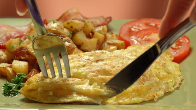vídeos de stock, filmes e b-roll de cu cheese omelette with breakfast potatoes on a plate as knife slices through thick omelette and a fork picks up a piece - garfo