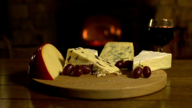 Cheeseboard with red wine in front of fire, DOLLY