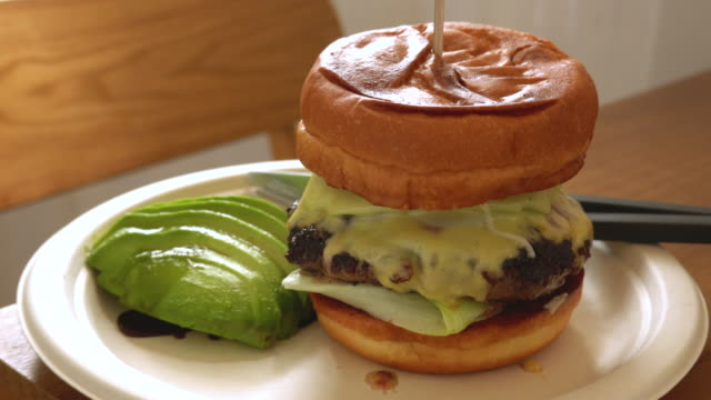 cheeseburger beef served with avocado. - cheeseburger stock videos & royalty-free footage