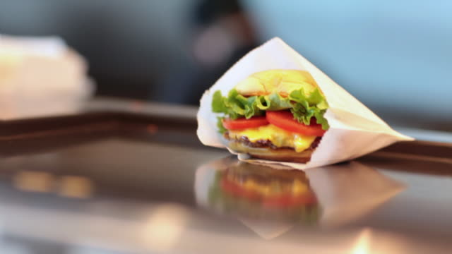 a cheeseburger in a wrapper - cheeseburger stock videos & royalty-free footage