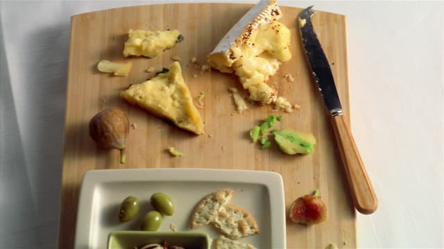 PAN cheeses and crackers leftovers on chopping board