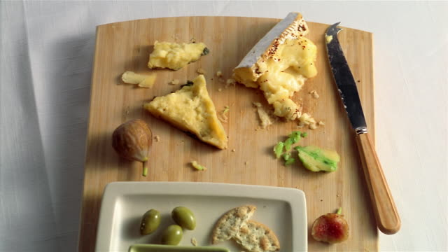 cheeses and crackers leftovers on chopping board - plate of food stock videos & royalty-free footage