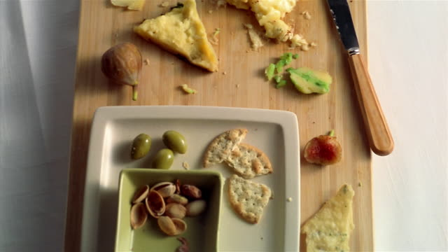 TU, TD cheeses and crackers leftovers on cupping board