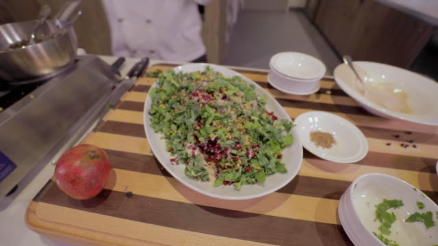 chef adding cooked pine nuts to a fresh salad - quinoa salad stock videos & royalty-free footage