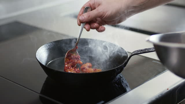 chef adding marinaded prawns to hot skillet - human hand stock videos & royalty-free footage