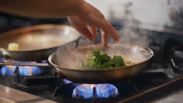 Chef adds leafy greens to corn mix and flips skillet over burning stove top in restaurant kitchen