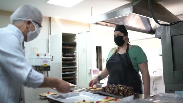 vídeos de stock e filmes b-roll de chef and assistant preparing cakes and dessert - arranjo