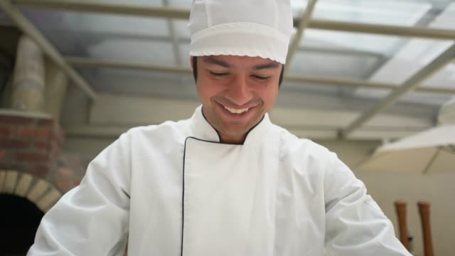 Chef at an italian restaurant making a pizza using a metallic rolling pin smiling