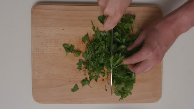 chef chopping dill on a wooden cutting board in kitchen - dill stock videos and b-roll footage