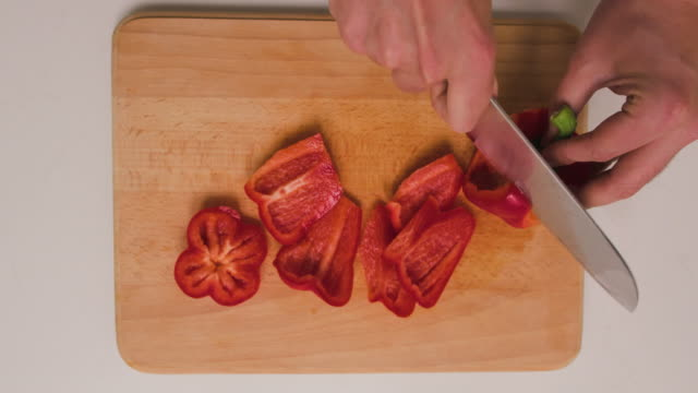 Chef chopping pepper on a wooden cutting board in kitchen