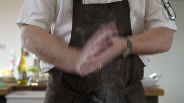 Chef clapping flour off his hands