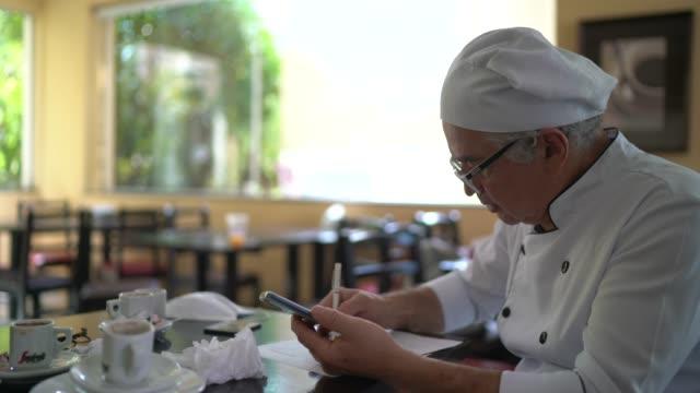 chef kontrolliert die finanzen des restaurants - kochberuf stock-videos und b-roll-filmmaterial